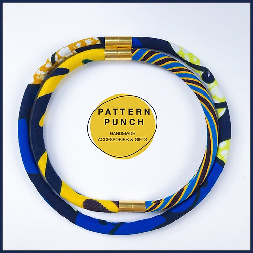 Lightweight fabric rope necklace with magnetic clasp in blue and yellow African print fabrics.