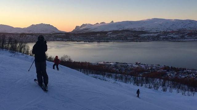 Skiing in Norway overlooking the ocean at sunset