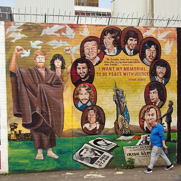 Wall with mural depicting hunger strikers with quote by Frank Stagg.