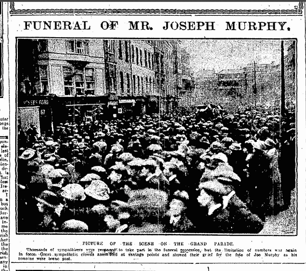 Crowds on Grand Parade, Cork city, with funeral procession in background.