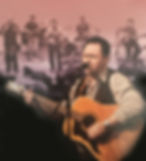 Russ singing on stage with his guitar and other and members behind him