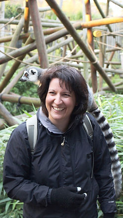 Sara smiling with a lemur on her shoulder