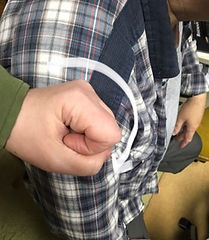 Russ's shoulder with fist and arrow showing Social-Haptic sign for coffee
