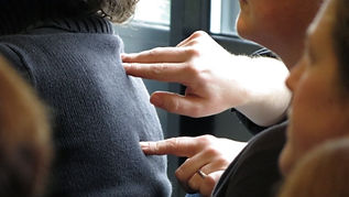 Close up image of hands performing Social-Haptic messages on a lady's back