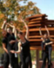 """A group of dancers dressed in black raise their arms in front of IKD's sculptural insallaion, """"Conversation Plinth"""" on the library plaza in Columbus, Indiana, USA"""