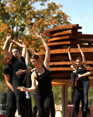 "A group of dancers dressed in black raise their arms in front of IKD's sculptural insallaion, ""Conversation Plinth"" on the library plaza in Columbus, Indiana, USA"