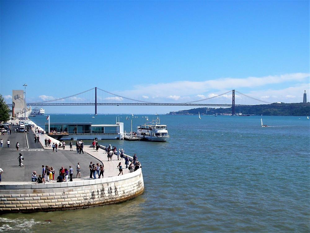 משמאל ניתן להבחין באנדרטת המגלים; ברקע גשר 25 באפריל; מימין מונטה כריסטו - הפסל של ישו שבצידו השני של הנהר.