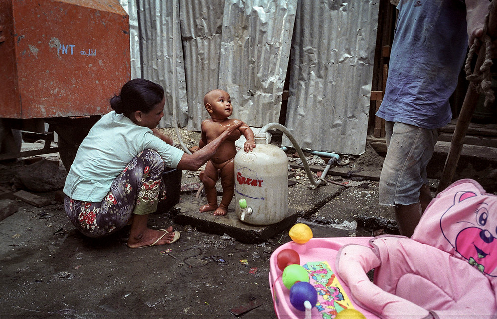 A woman gives her little son a wash on the side of the street in Yangon, Myanmar