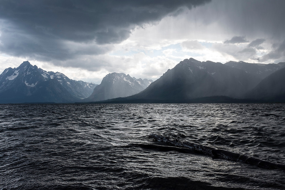 storm clouds over mountains with lake in foreground