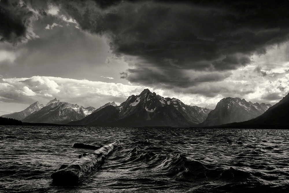 Dark storm clouds over mountains with log floating in lake