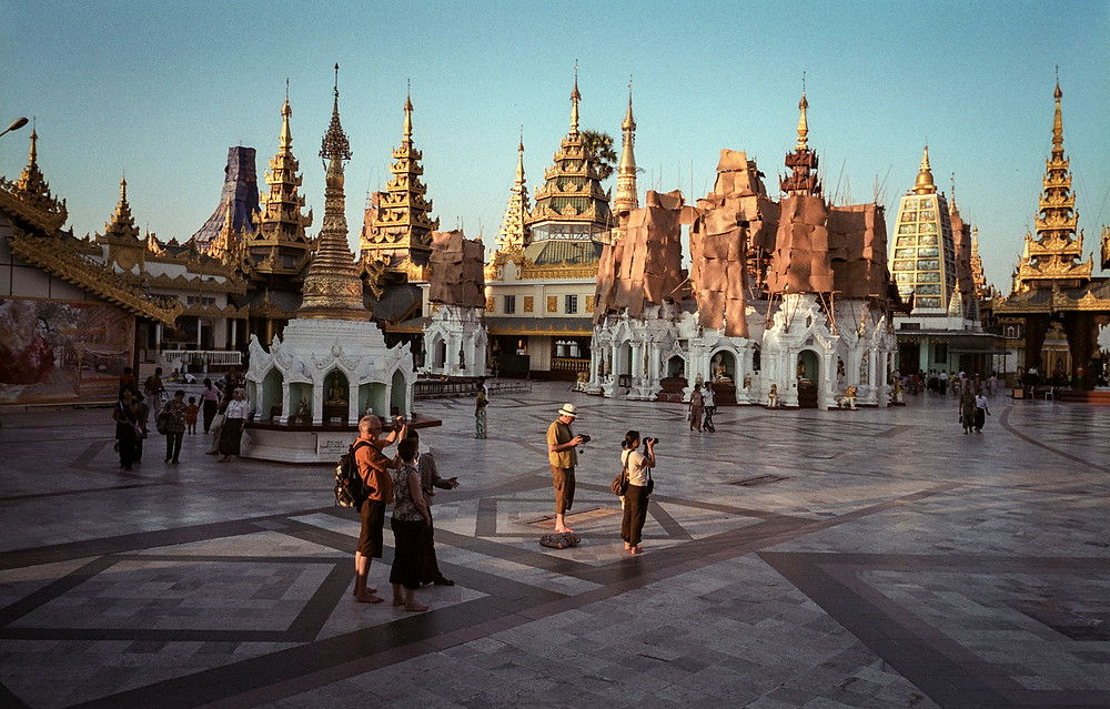 Western tourists taking photos in the grounds of the Shwedagon Pagoda in Yangon, Myanmar