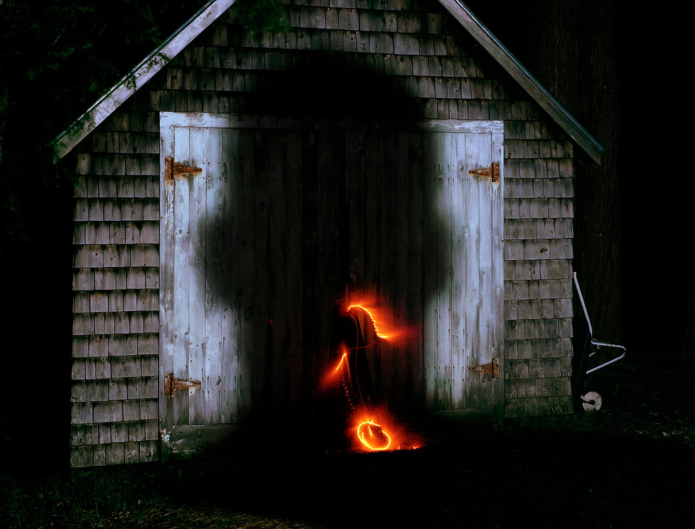 A dark image of the massive shadow of someone's head, along with light produced by what seems to be fire crackers.
