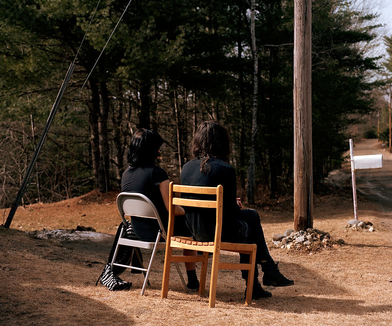two women with brown hair sitting on two chairs in a forest, showing us their back.
