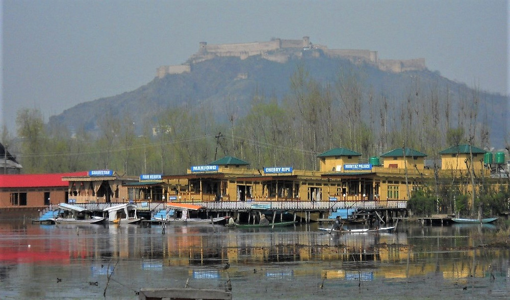 Dal Lake with it's many house boats reflected in the water, in the background a large monastery sitting on the mountain.