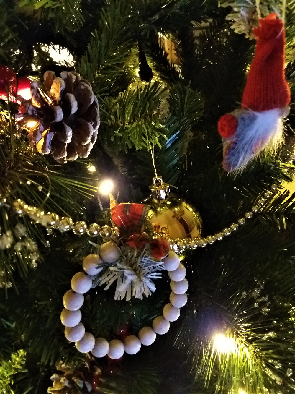 A wooden bead hoop with red tartan ribbon Christmas tree decoration