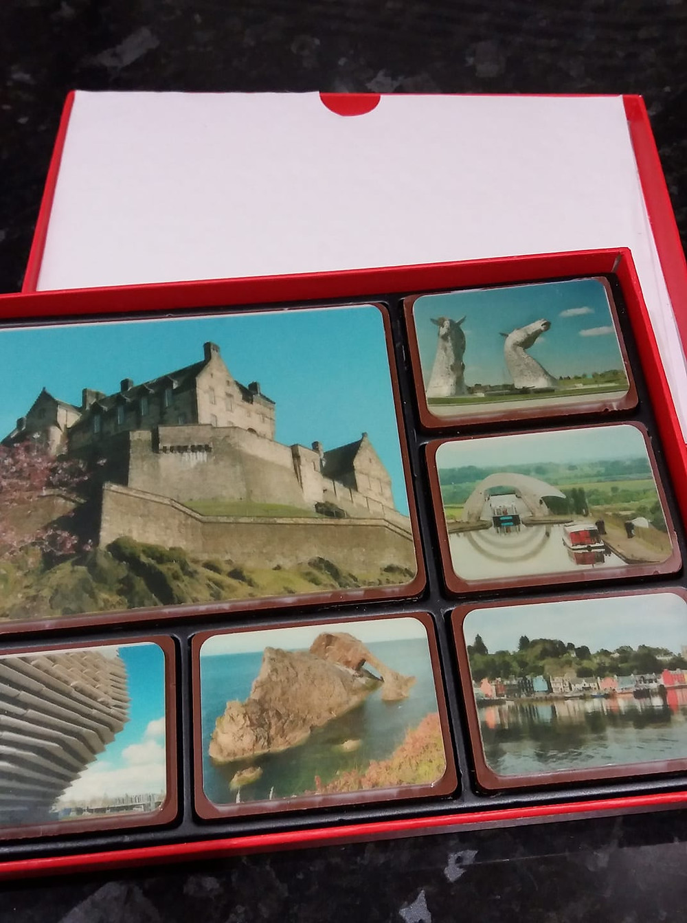 ChocFACE open box of image printed Belgium chocolates with Scottish landmarks including Edinburgh Castle, V & A Dundee, The Kelpies, Falkirk Wheel and the colourful houses of Tobermory on the Isle of Mull.