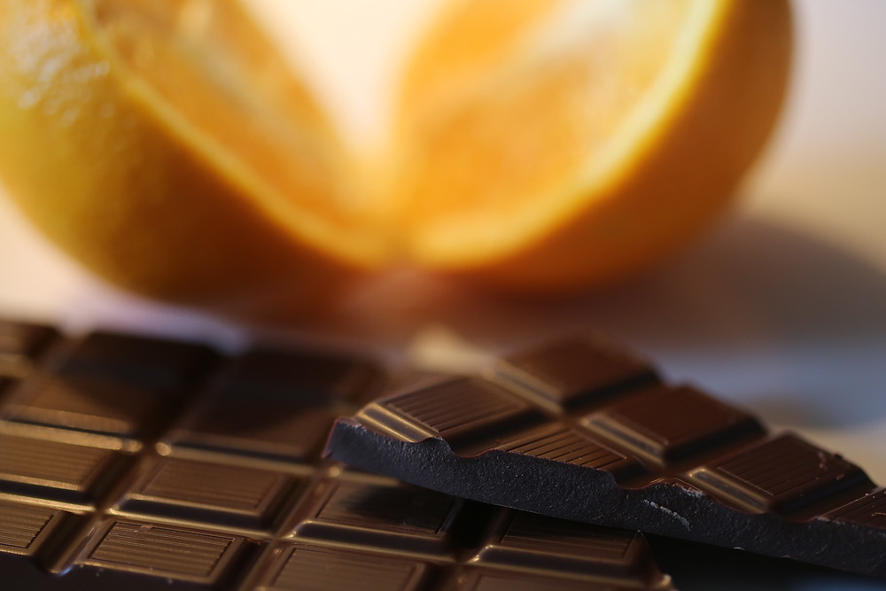 Close up of chocolate bar and sliced orange in background.