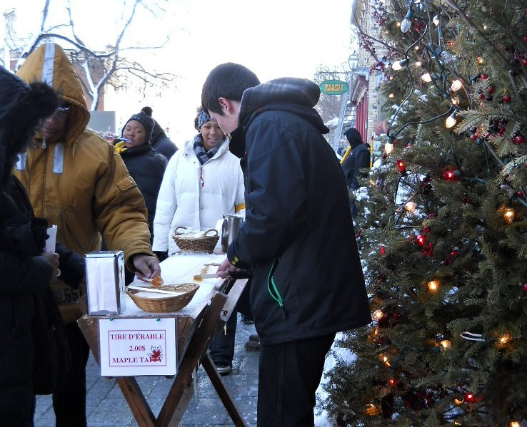 Street stand covered in snow to make and buy a maple taffy