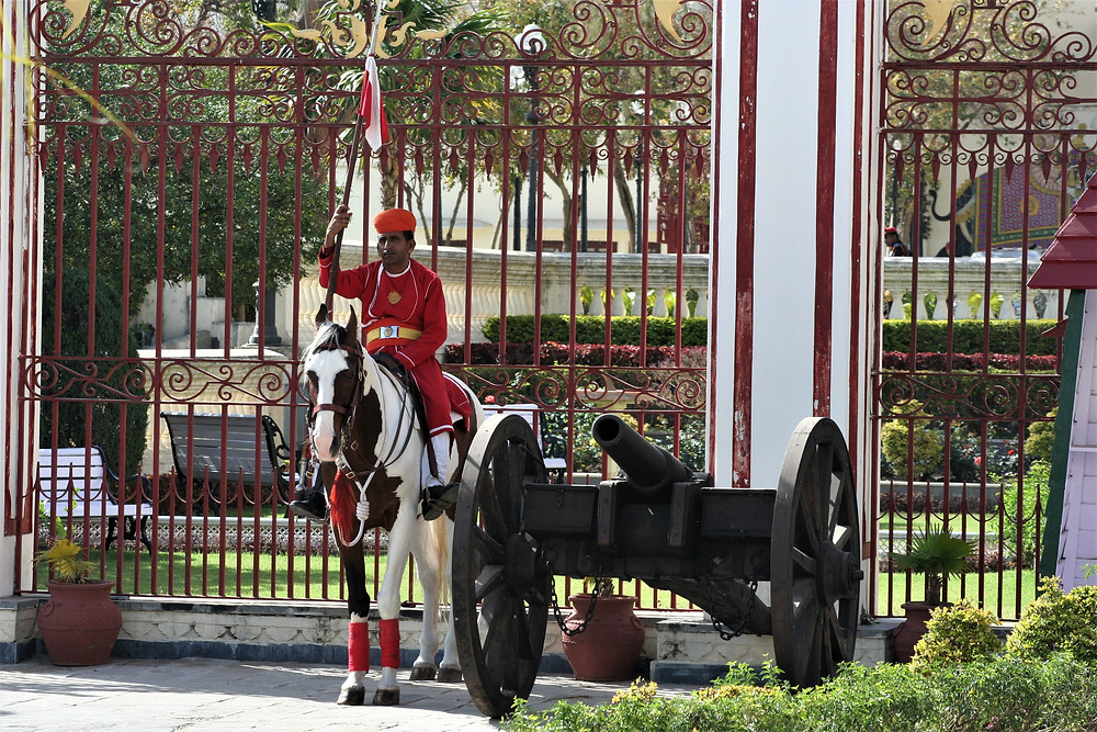 Guard in red uniform, sat on brown and white horse holding a flag by a historical firing gun, outside the gates of Fateh Prakesh Palace, Udaipur, India