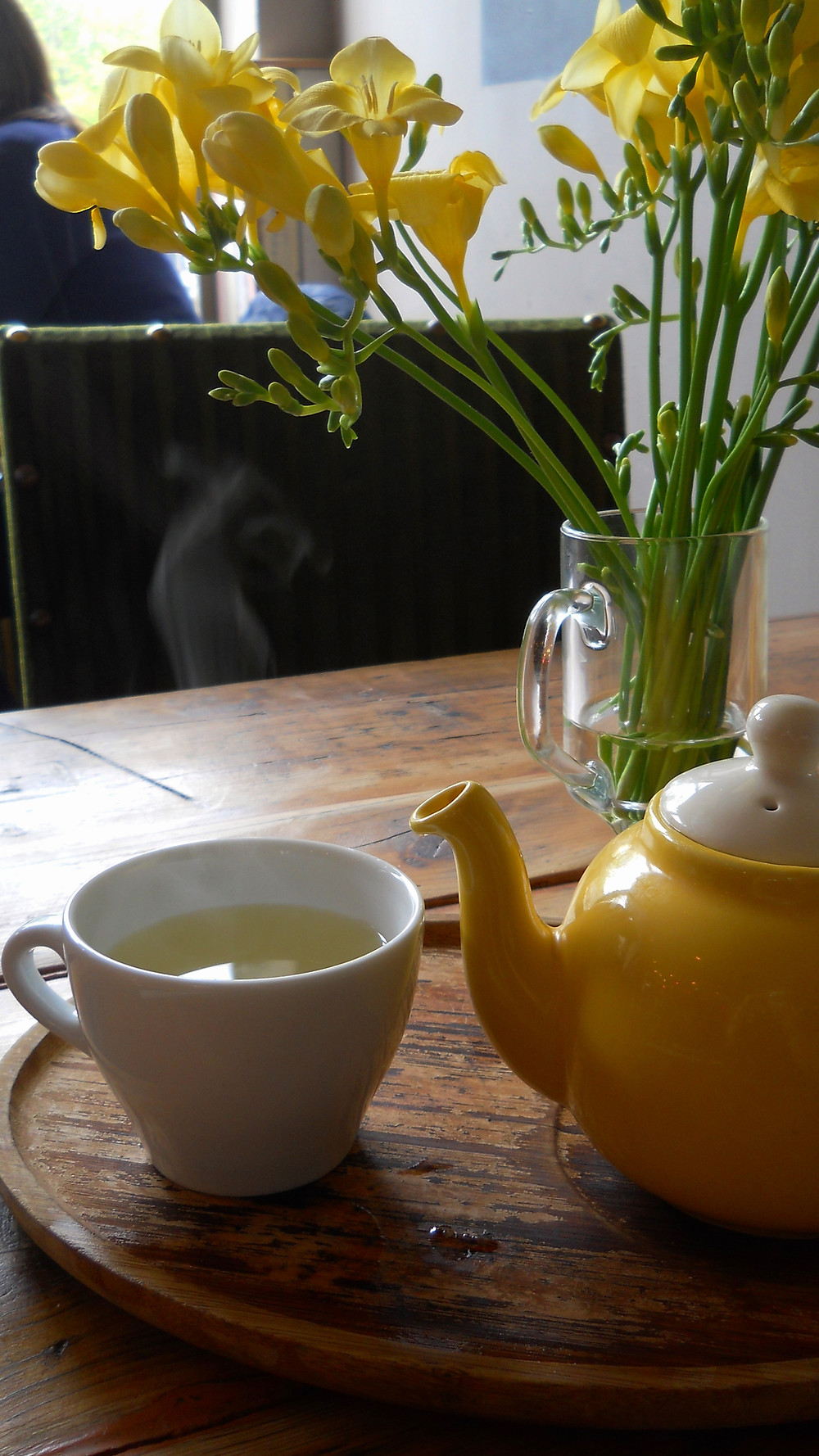 Freshly brewed, pipping hot cup of tea with yellow tea pot and display of bright yellow freesia flowers. l