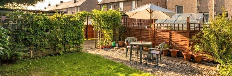 Garden furniture on decorative stones by lawn with wooden panelled fence to the back and trellis/arch covered in climbers.