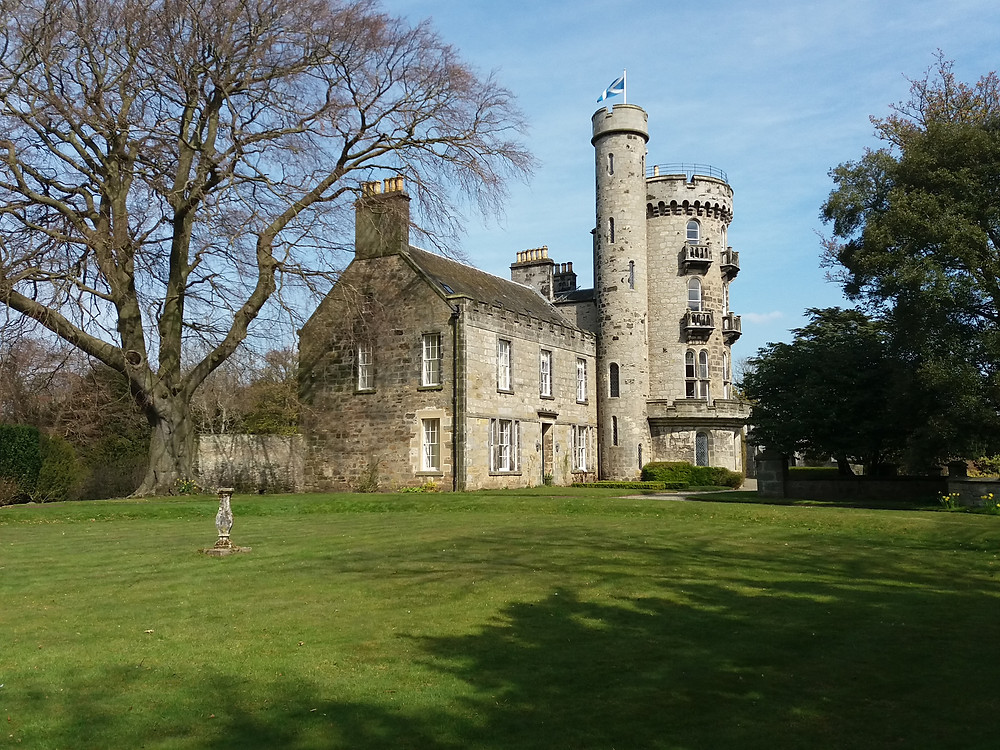 Historic Stately Home - House of Binns, surrounded by a manicured lawn and trees.