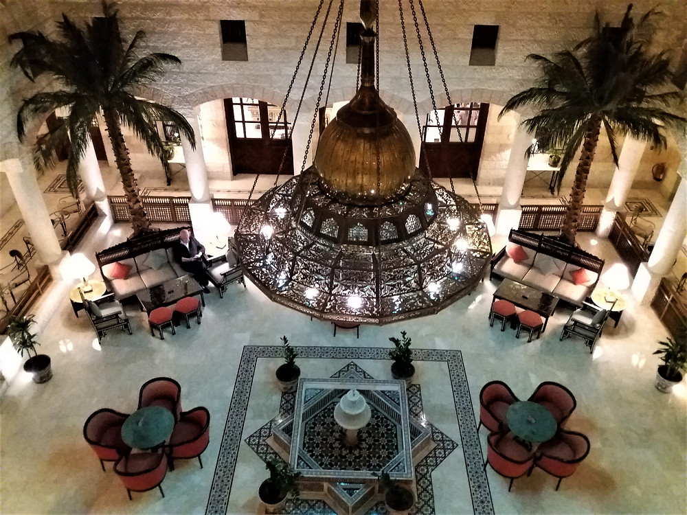 Movenpick Resort Petra Interior courtyard lounge area with it's high ceiling, large brass ornate chandelier, palm trees and smoothing water fountain.