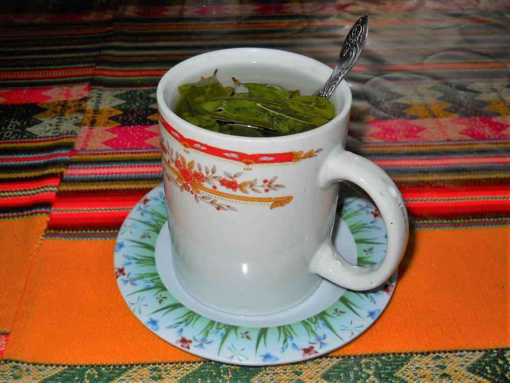 A mug of Peruvian Coca Leaf Peruvian tea, sat on a colourful Peruvian table cover.