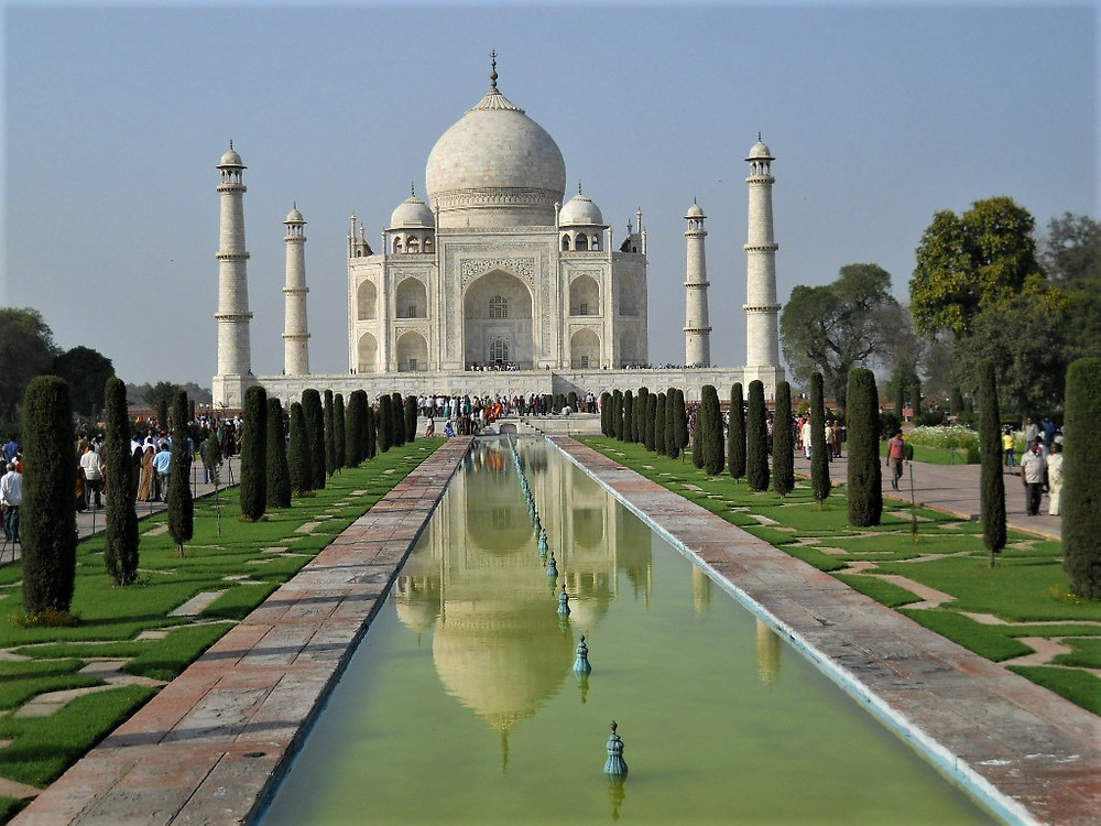Image of Taj Mahal, with reflection in water feature, lined by upright small evergreen trees.