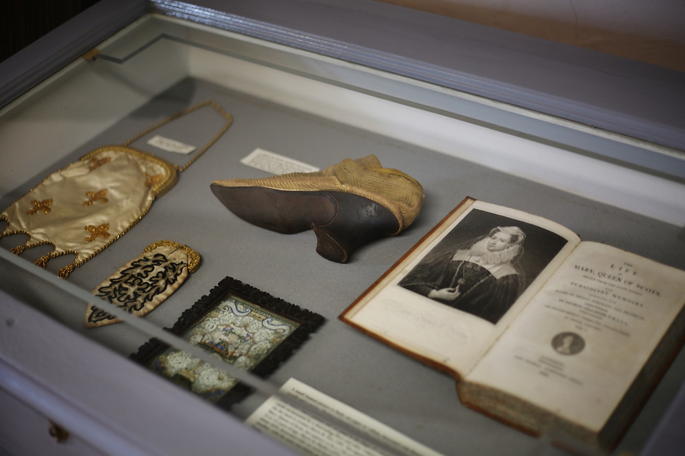Items on display belonging to Mary Queen of Scots. Items include a shoe, small bag and purse.