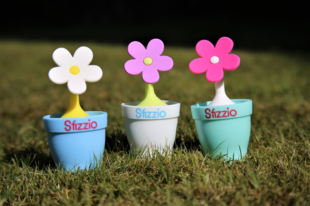Three brightly different coloured flower potted tea infusers on the lawn.