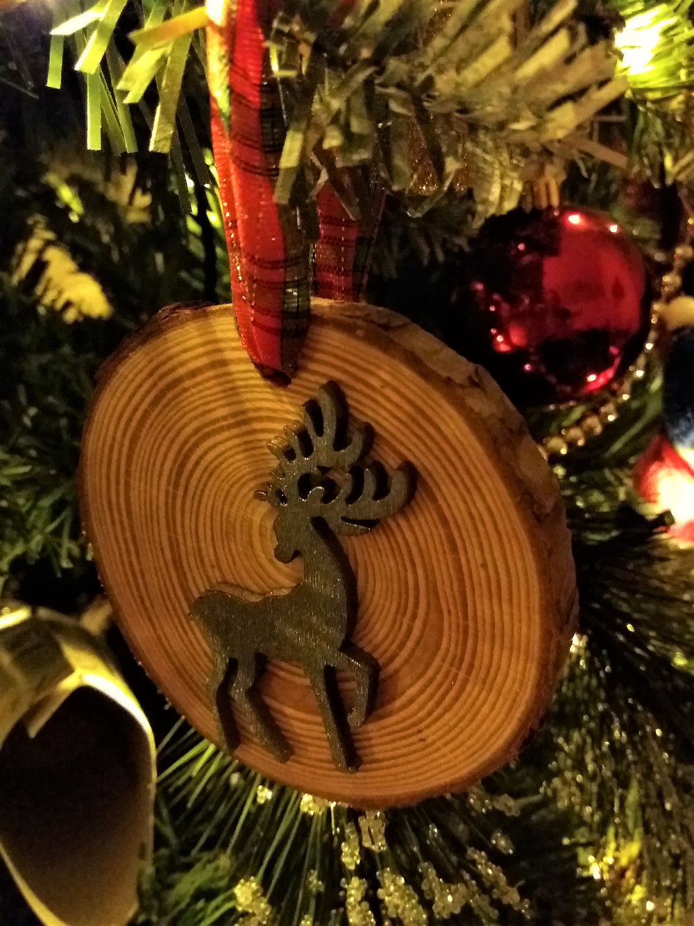 Wooden reindeer spray painted silver and glued to wooden disc. Then completed with tartan ribbon to hang on Christmas Tree