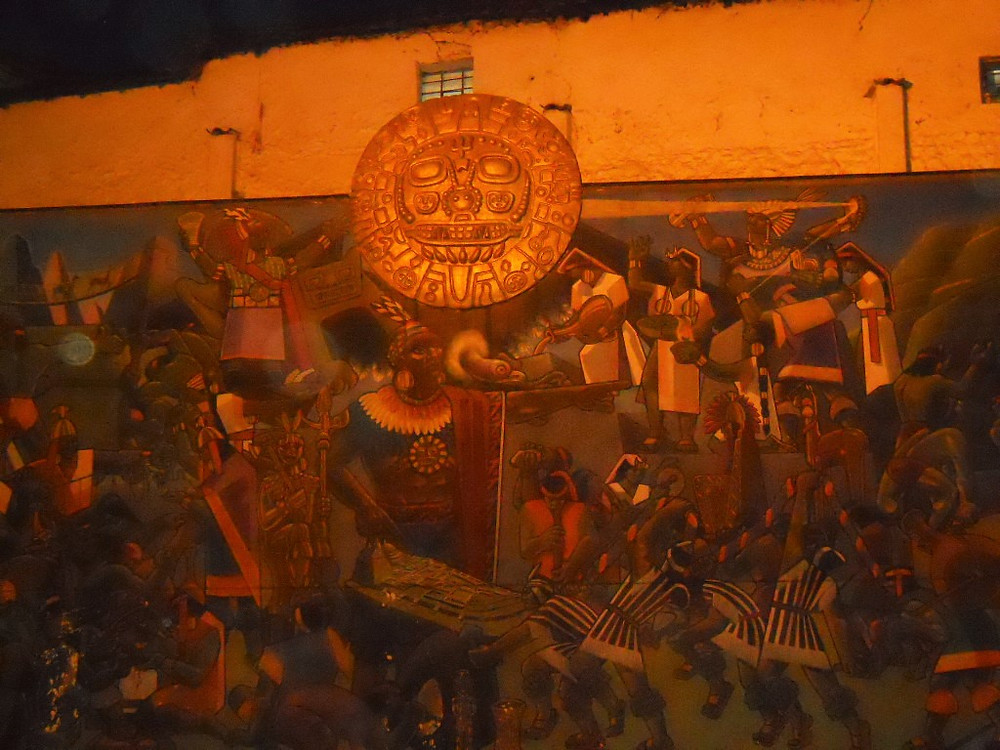 Traditional Inca Mural showing life celebrations and rituals with a gold sun shield ornament.