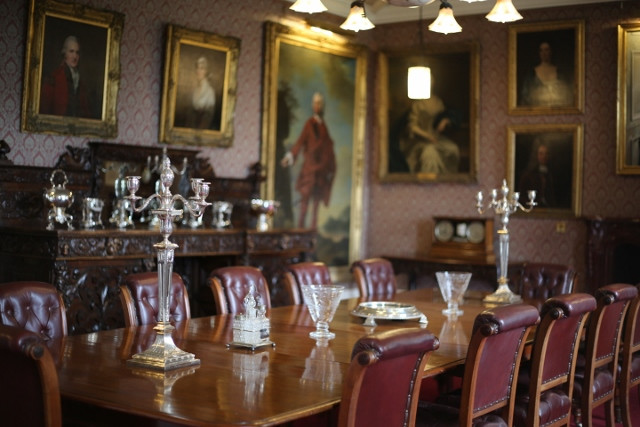 Large banquet table with decorative silverware. In the background family MacLeod portraits.