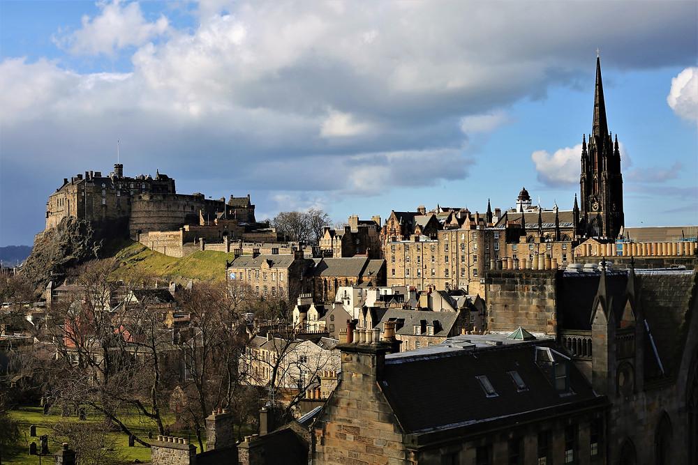 View across Edinburgh city skyline rooftops stands Edinburgh Castle.