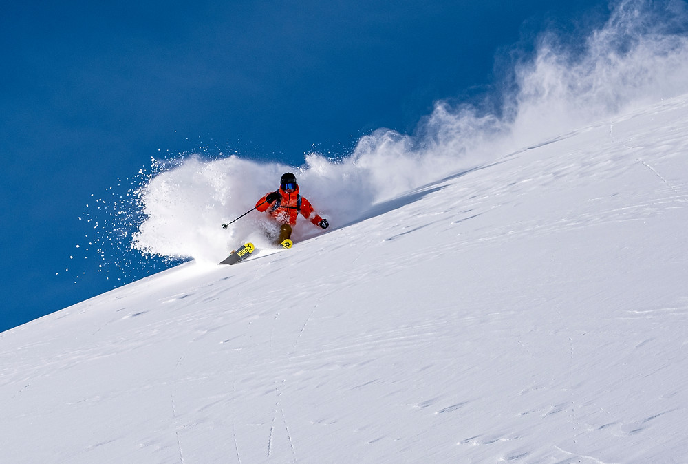 Skiing Action Shot With white Powder Snow and Bright Blue Sky