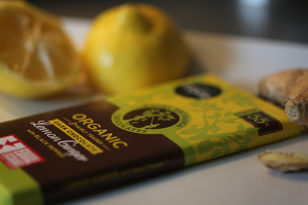 Close up of wrapped Equal Exchange Organic Dark Chocolate and Lemon Ginger with Black Pepper bar, as well as sliced lemon in the background.