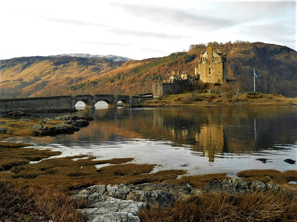 Eilean Donan Castle surrounded with autumn colours and reflection in the loch.