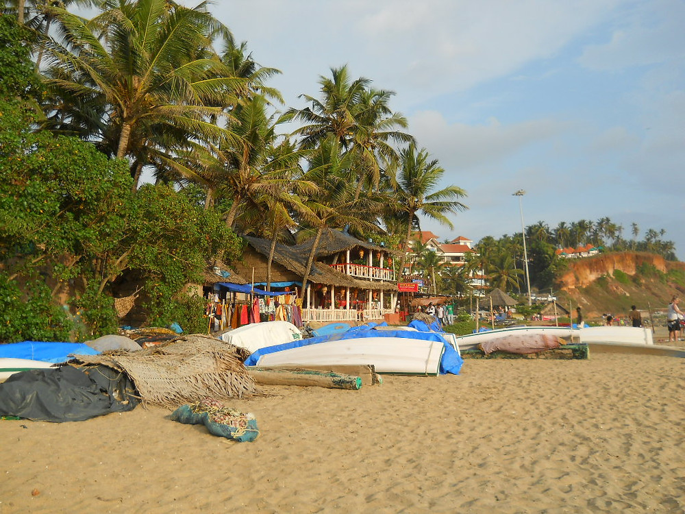 Varkala Beach, at the back lined with small boats, restaurants, craft selling huts and coconut palm trees.