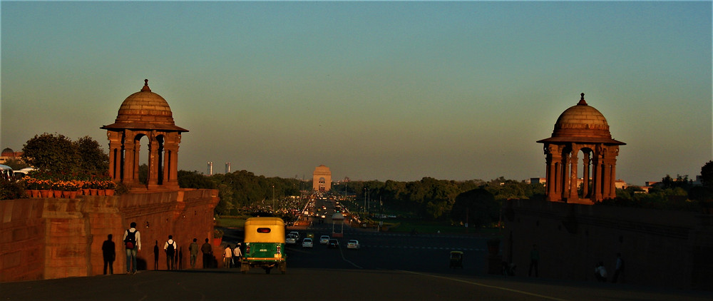 Sunset at India Gate with tuk tuk, people and traffic.