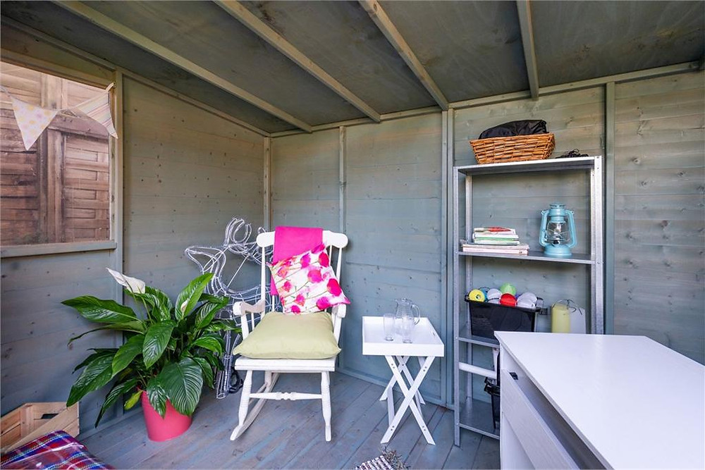 Office desk, shelfing, standing tray, chair and large peace lily inside garden summer house.