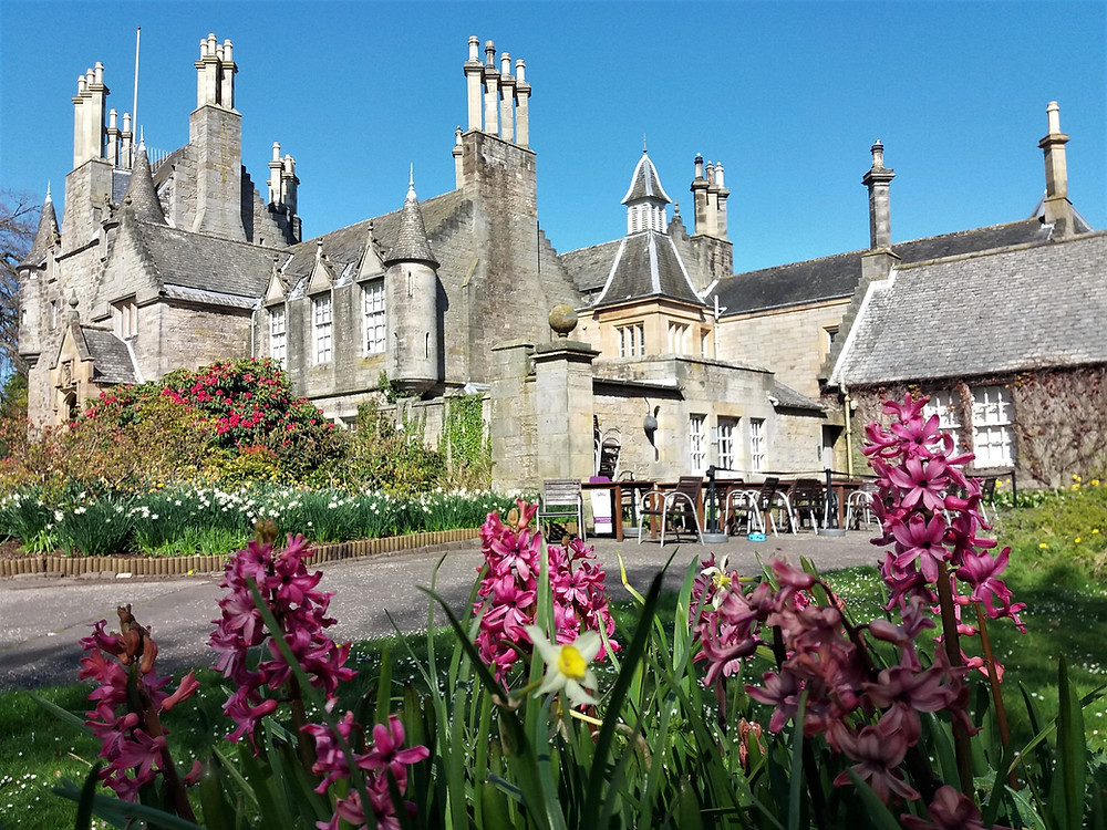 Lauriston Castle with bright blue clear sky and spring flowers in foreground.