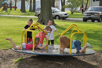 Children playing on merry-go-round at the park