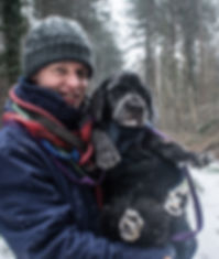 man in the snow carrying dog