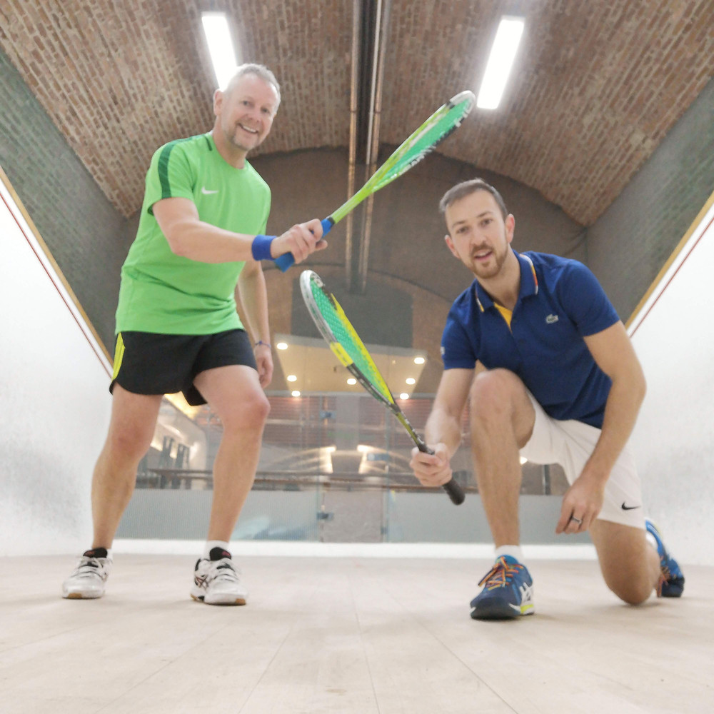Older and Younger man playing squash
