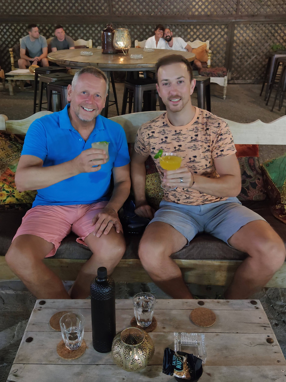 Age gap gay men with cocktails sitting on bench
