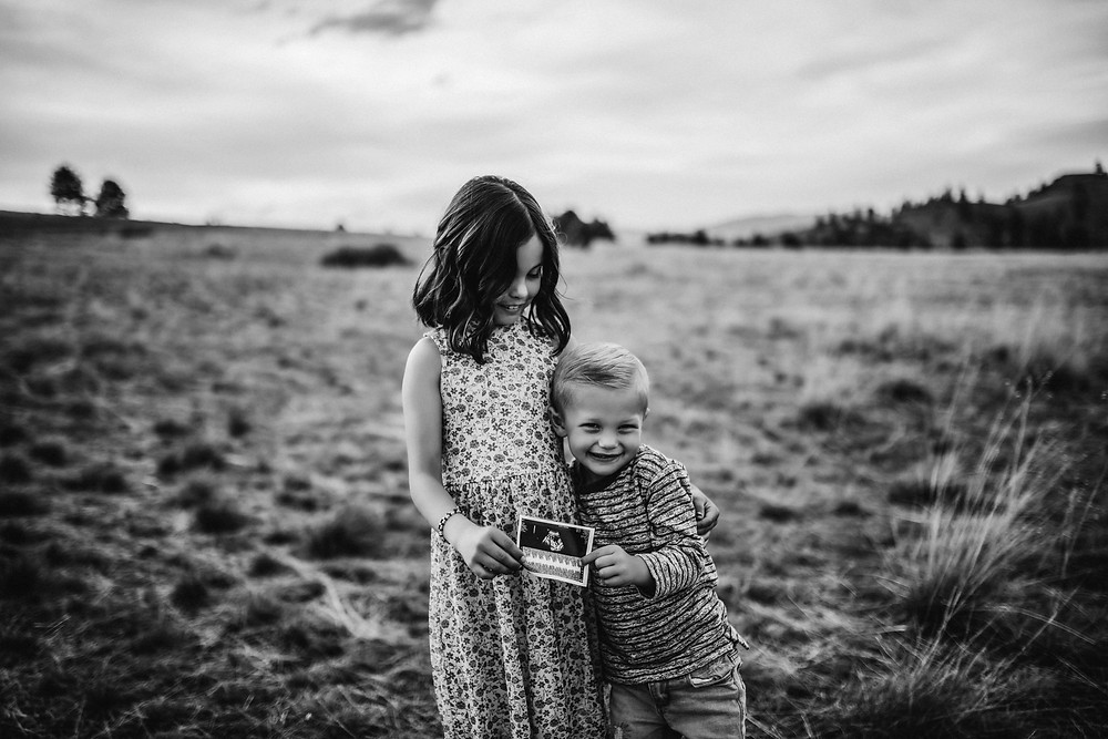 Family poses for their baby announcement session in Missoula, Montana, captured by Infinite Photography and Film
