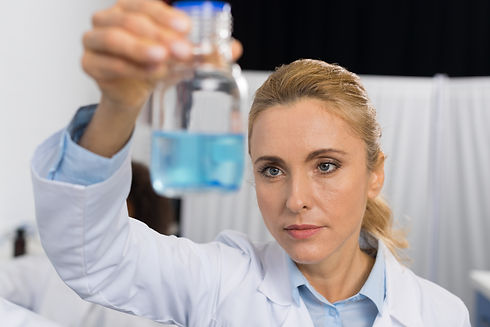 female-scientist-examine-flask-with-blue