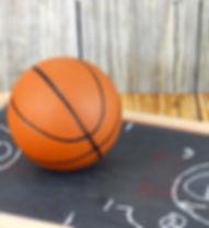 An orange basketball on a wood floor in