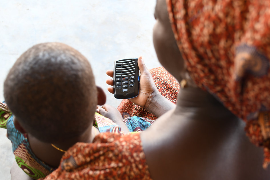 African Woman with Child listening to Bible Plus Unit